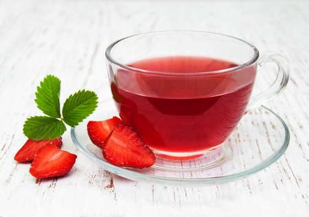 leaves green: Fruit tea with strawberries  on a wooden table