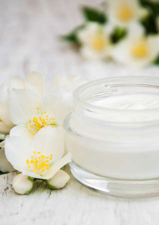 day care: face and body cream moisturizers with jasmine flowers on white wooden background Stock Photo