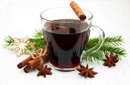 Glass of mulled wine with spices on a old wooden background