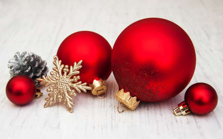 red and white: red christmas balls with ribbon on a wooden background