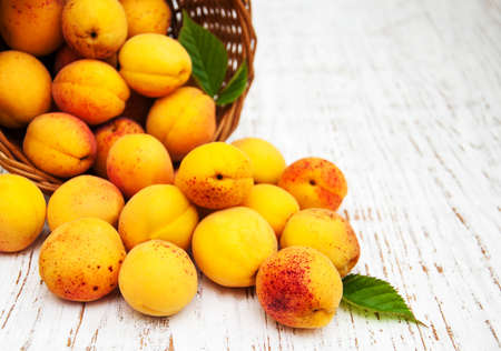 basket: Basket with apricots on a old wooden background Stock Photo