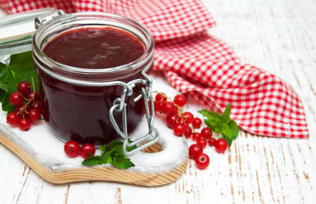preserving: Redcurrants  jam  with fresh berries on a wooden background Stock Photo