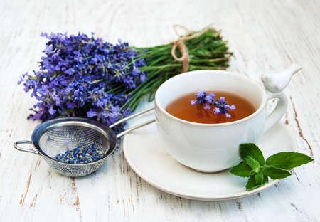 오래된 나무 배경에 차와 라벤더 꽃의 컵 스톡 콘텐츠