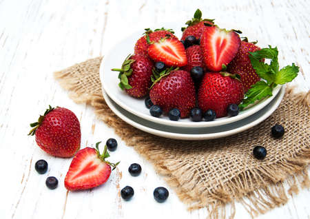 strawberry: plate with blueberries and strawberries on a old wooden background Stock Photo