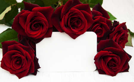 text space: Fresh Red roses and greeting card on a wooden background