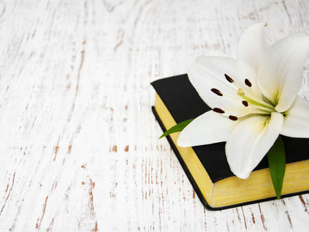 religious text: easter lily and bible on a old wooden background Stock Photo