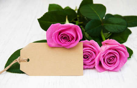 text space: Pink Roses with a card on a old wooden background Stock Photo