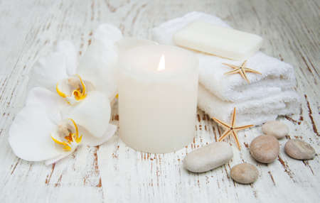 massage stones: White orchids, candle and massage stones on a wooden background Stock Photo