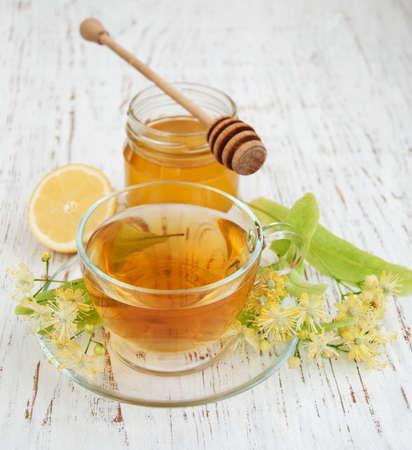 lemon: taza de t� de hierbas con flores de tilo en un fondo de madera vieja Foto de archivo