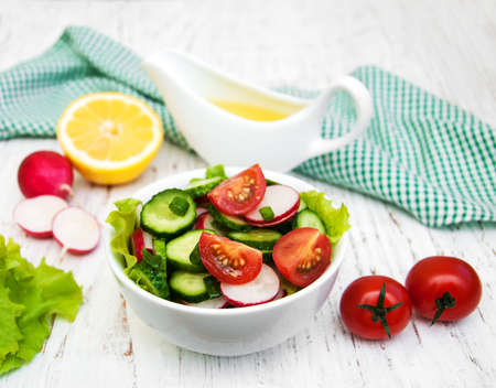 fruit plate: Spring salad with tomato, cucumbers and radish on a wooden background Stock Photo
