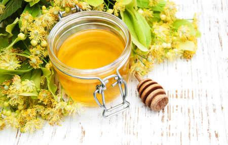 tilo: Tarro con la miel de tilo y flores sobre un fondo de madera