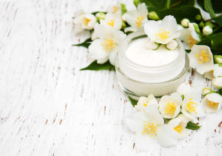 face and body cream moisturizers with jasmine flowers on white wooden background Standard-Bild