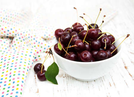 sour cherry: Bowl with cherries on a old wooden background