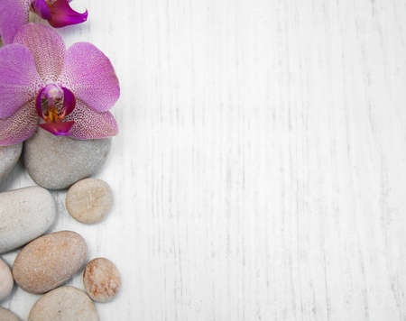 Orchids and massage stones on a wooden background