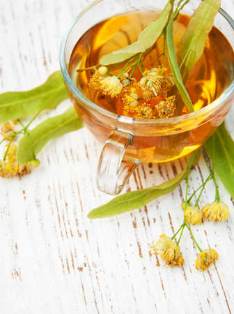 herbal: cup of herbal tea with linden flowers on a old wooden background