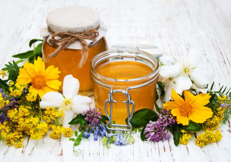 golden honey: Honey and wild flowers on a wooden background