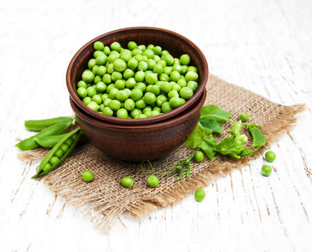 sweet sugar snap: Bowl with fresh peas on a wooden background Stock Photo