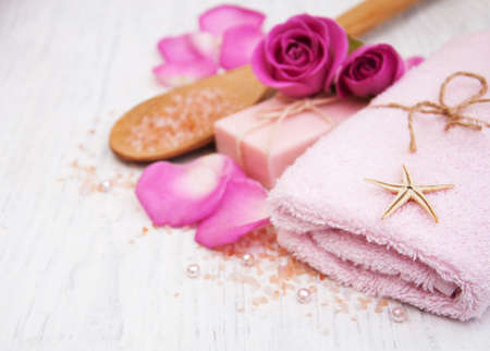 sal: Bath towels, salt and soap with pink roses on a old wooden background Foto de archivo