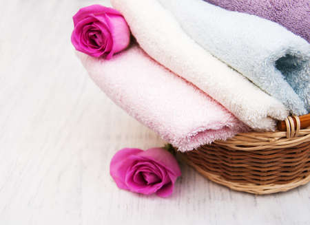 basket: Bath towels with pink roses on a old wooden background Stock Photo