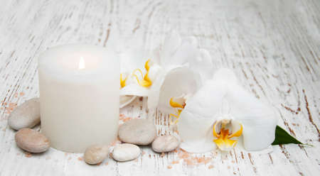 salon background: Candle, orcids and stones  on a wooden background