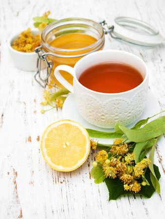 limón: taza de t� de hierbas con flores de tilo en un fondo de madera vieja Foto de archivo