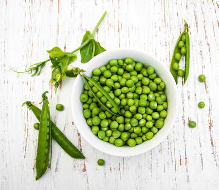 snap bean: Bowl with fresh peas on a wooden background Stock Photo