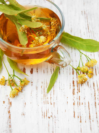 linden flowers: cup of herbal tea with linden flowers on a old wooden background