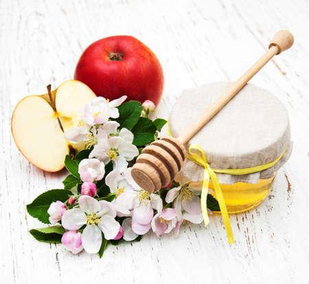 apfelbaum: �pfel mit Honig und Apfelbaum Blumen auf einem h�lzernen Hintergrund