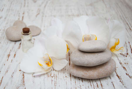 white orchids: White orchids, oils and massage stones on a wooden background