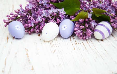 오래된 나무 배경에 부활절 계란과 신선한 라일락 꽃