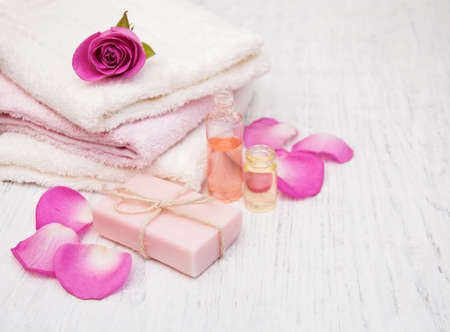 white towel: Bath towels and soap with pink roses on a old wooden background Stock Photo