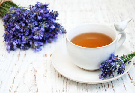 breakfast cup: Cup of tea and lavender flowers on a old wooden background