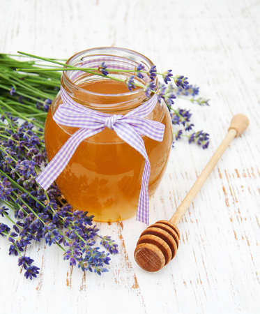 wood stick: Honey and lavender flowers on a old wooden background