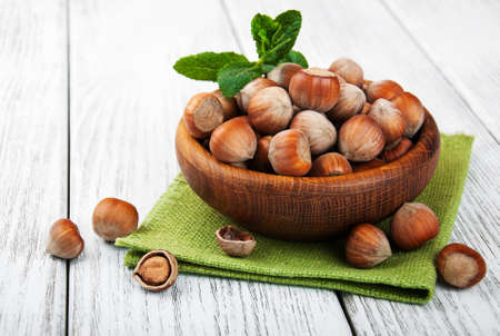 Bowl with hazelnuts on a old wooden table Stock Photo