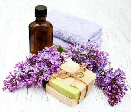 天然の手作り石鹸と木製の背景にライラックの花