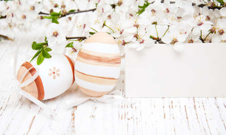 Easter eggs, greeting card and cherries blossom on a old wooden background