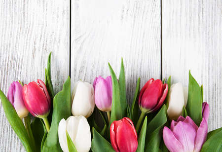 bouquet of fresh spring tulips -  flowers floral border on a wooden background