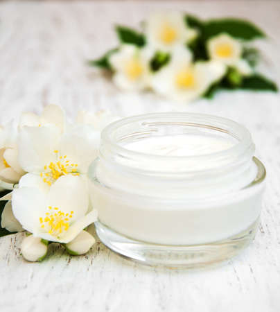 moisturizers: face and body cream moisturizers with jasmine flowers on white wooden background Stock Photo
