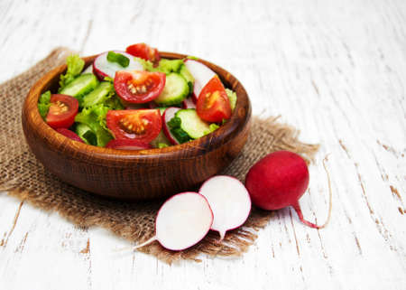 tomate ensalada: Spring salad with tomato, cucumbers and radish on a wooden background Foto de archivo