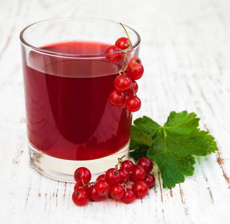 redcurrant: Glass of redcurrant lemonade on a old white wooden background Stock Photo