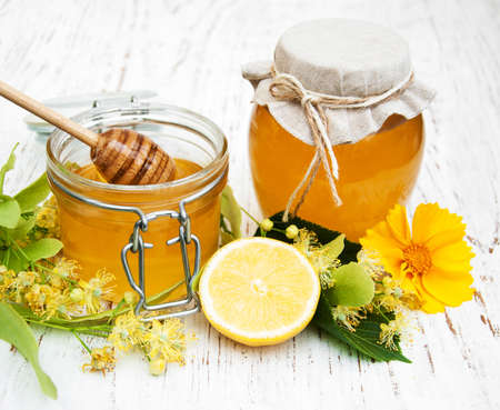 tilo: Jars with honey and linden flowers on a wooden background