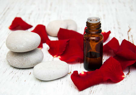 rose flower petals with aromatherapy essential oil glass bottle