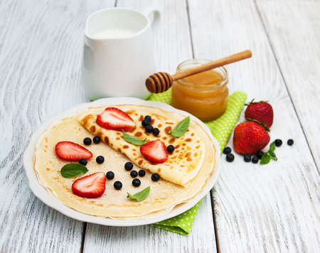 pancakes  with strawberries and blueberries  on the old table