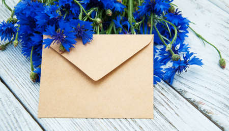 old envelope: Blue fresh cornflowers with envelope on a old wooden table