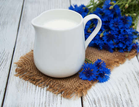 Jar of milk and cornflowers on a old wooden table Stock Photo