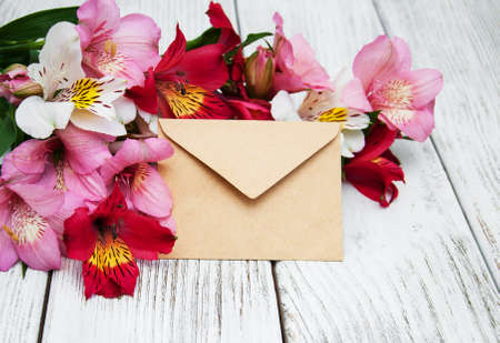 old envelope: blank paper envelope with alstroemeria flowers on old wooden table Stock Photo