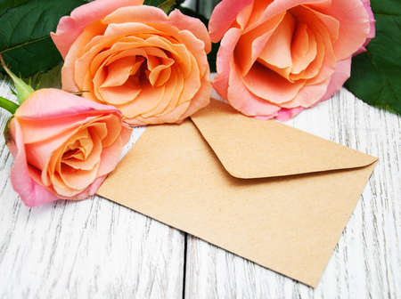 old envelope: Pink roses and envelope on a old wooden background Stock Photo