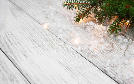 evergreen: christmas tree branch and lights on wooden background