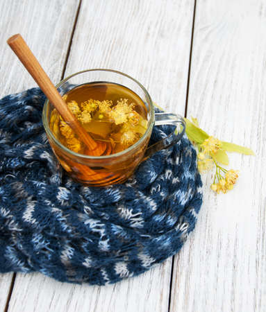linden tea: Scarf and Linden tea with honey on a wooden table Stock Photo