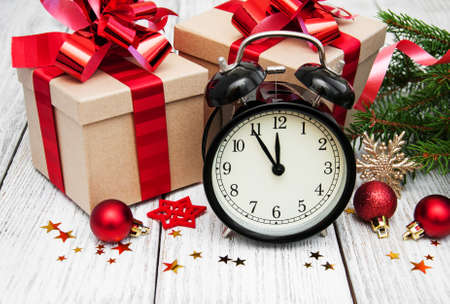 christmas clock on a  wooden background with fir tree and gift boxes Stock Photo